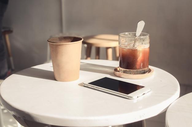 コーヒーショップのテーブルにコーヒー、電話、スカッシュ