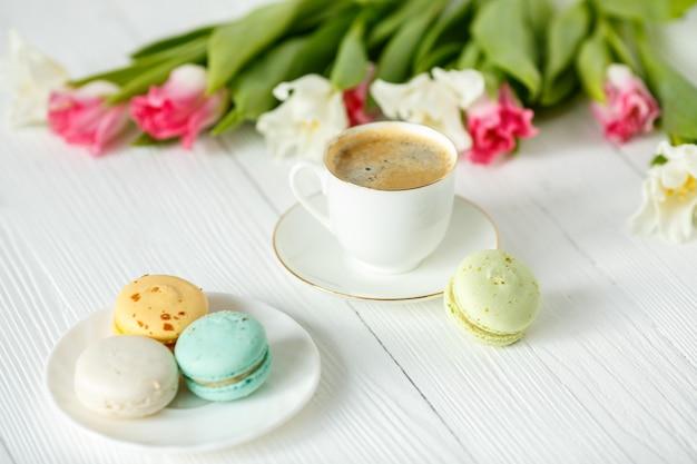 Кофе, розовые и белые тюльпаны и macarons на белом деревянном столе. завтрак. перерыв на кофе.