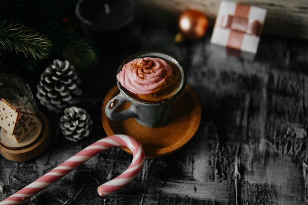 Coffee, pink marshmallow, fir branch, pine cone, gift box, candy cane on dark backdrop. christmas drink