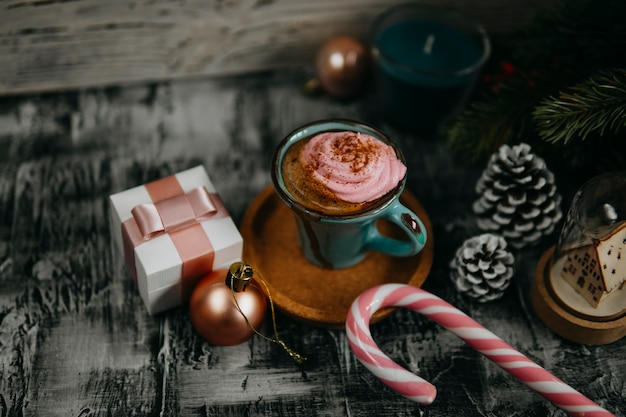 Coffee, pink marshmallow, fir branch, pine cone, gift box, candy cane on dark backdrop.