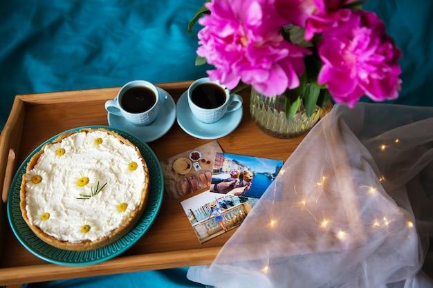 コーヒー、ピンクの牡丹、木製トレイ、トップビューでチーズケーキ。
