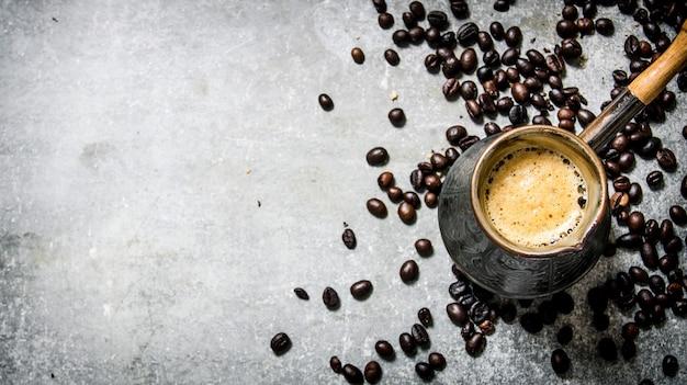 Кофейник и жареный кофе вокруг.