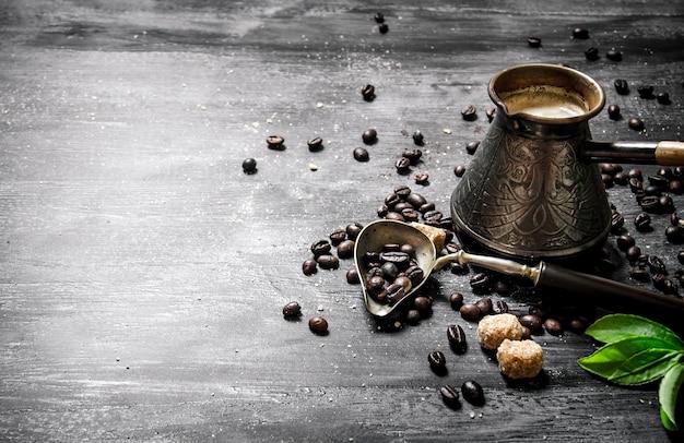 Кофейник с кофейными зернами, тростниковым сахаром и свежими листьями. на черной доске.