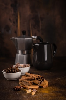 Coffee pot with spices on brown background.