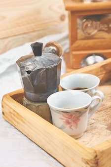 Coffee pot with two cup of coffe on wooden tray