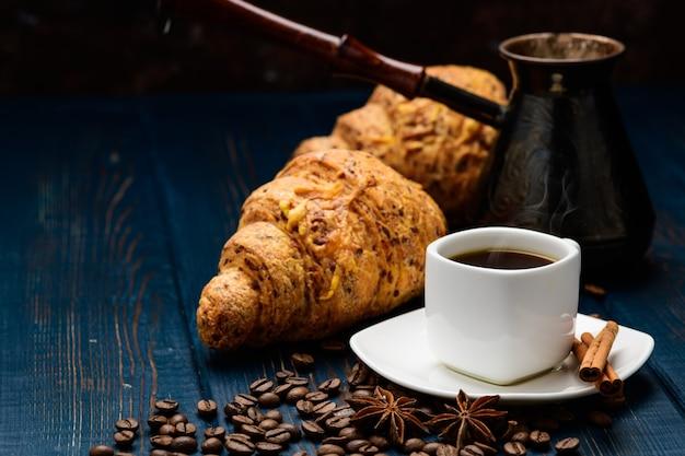 コーヒー豆とクロワッサンが入った青い木製のテーブルの上のカップにコーヒーが注がれます。