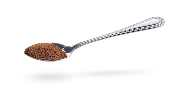 白い背景で隔離のスプーンでコーヒー粉