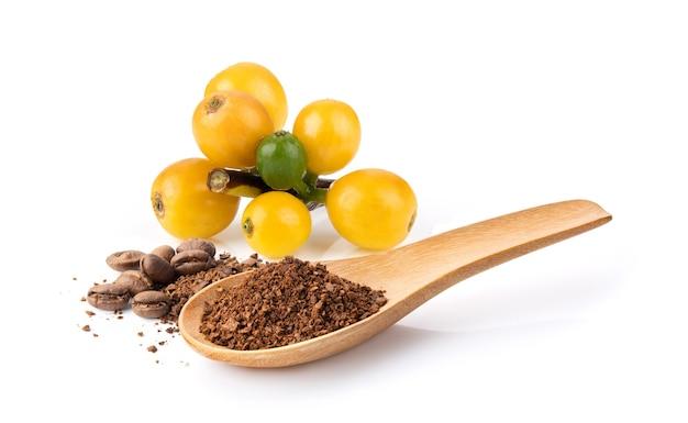 木のコーヒー粉と白い背景で隔離の新鮮な黄色のコーヒー豆