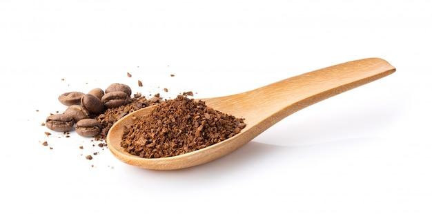 Кофейный порошок в деревянной ложкой на белом