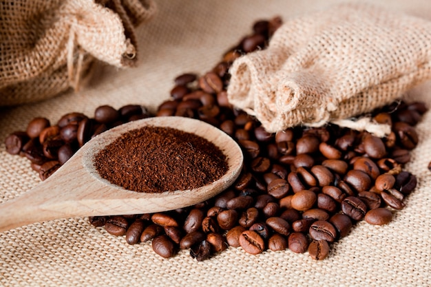 Кофейный порошок на деревянной ложке, с мешком из ткани рафии, коричневый фон