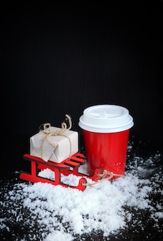 Coffee in red cup with christmas present on black background