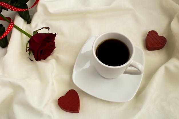 コーヒー、赤いハート、白いベッドでローズ