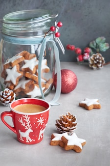 Coffee in red xmas cup and tasty star ginger cookies in a glass jar with winter decorations