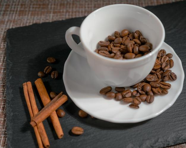 茶色の表面に白いセラミックマグカップにシナモンスティックを入れたコーヒー焙煎豆、クローズアップ