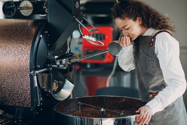 커피 로스터기와 바리스타는 커피 로스팅 과정에서 볶은 원두 냄새를 맡습니다.