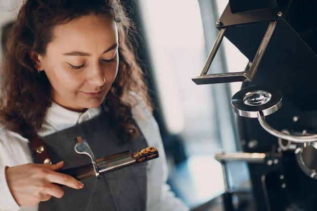 커피 로스터기 및 바리스타는 커피 로스팅 과정에서 트라이어와 함께 냄새를 맡습니다.