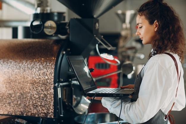 커피 로스터 기계와 커피 로스팅 과정에서 노트북을 들고 있는 바리스타 여성.