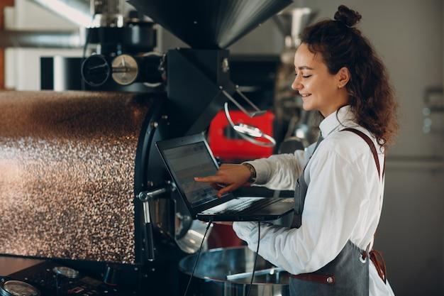 커피 로스터 기계와 커피 로스팅 과정에서 노트북 컴퓨터를 가진 바리스타 여성.