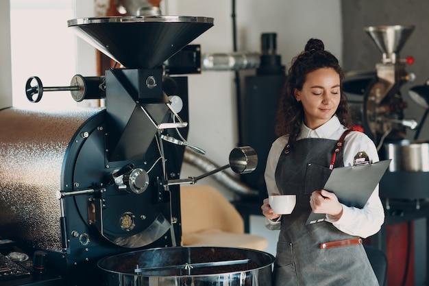 커피 로스터 기계와 태블릿이 있는 바리스타 여성은 커피 로스팅 과정에서 펜을 씁니다.