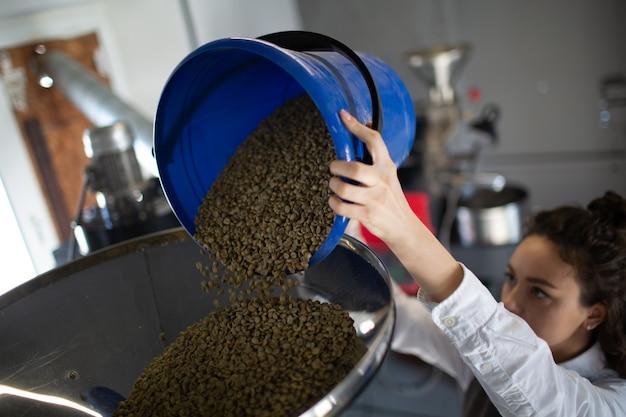 커피 로스팅 과정에서 커피 로스터 기계. 젊은 여성 작업자 바리스타가 녹색 커피 콩을 장치에 로드합니다.