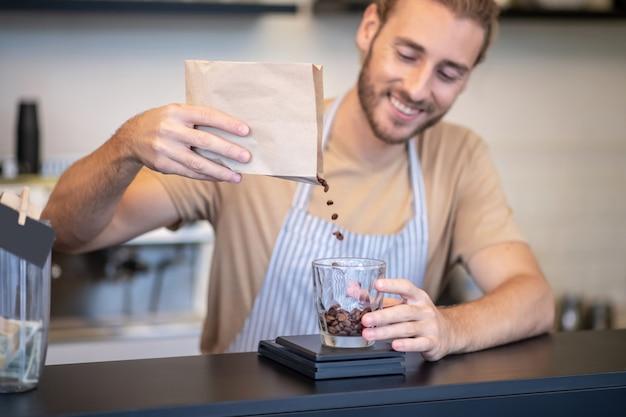 コーヒー、販売。コーヒー豆を注いで彼のカフェのバーカウンターで若い成人男性の笑顔