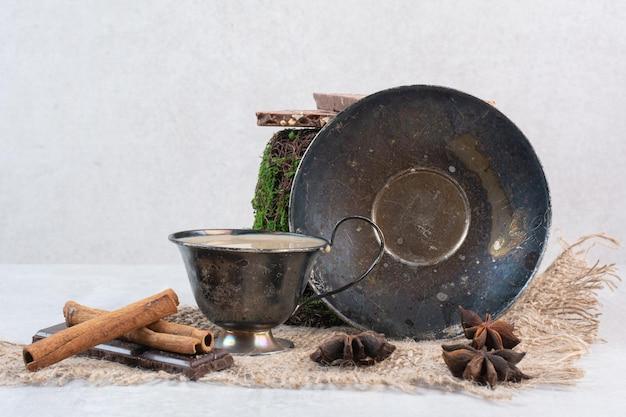 Кофе, блюдце, гвоздика и корица на мешковине