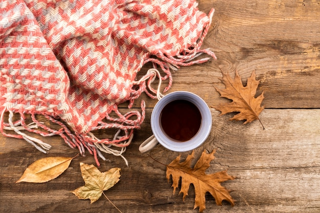 Coffee and scarf on wooden background