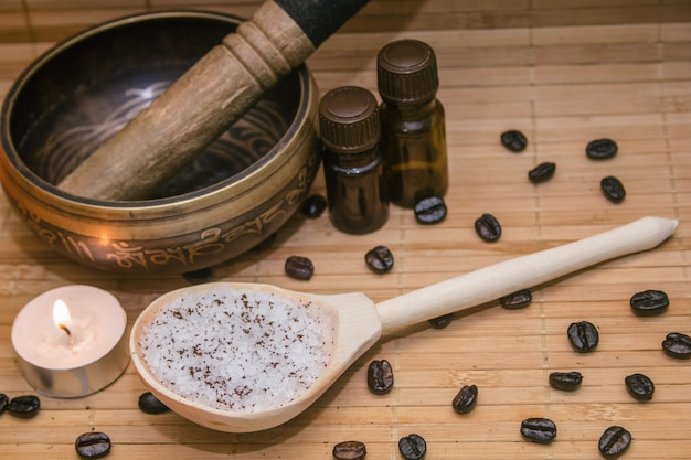 Coffee scrub, coffee beans, singing bowl, aroma oil, candle on straw mat