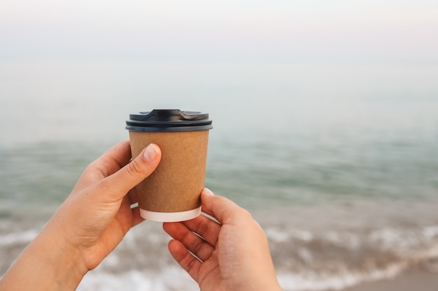 Coffee at the sea. young woman holds a disposable cup of coffee on on a sunny morning at the beach.