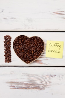 Coffee seeds arranged in a shape of heart. i love coffee break. white wooden planks on surface.