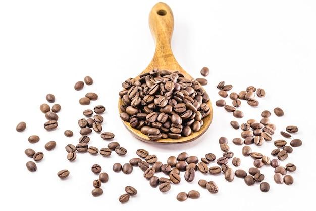木のスプーンのコーヒーの種、輸出タイプのブラジルのコーヒー、孤立した白い表面。
