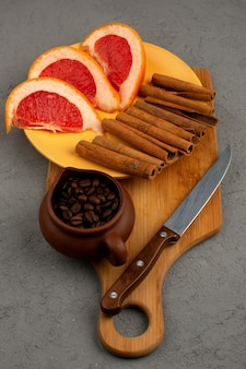 Coffee seeds inside brown pot along with grapefruit pieces and cinnamon on a grey desk