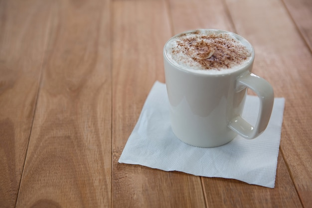 Кофе подается в белой кружке с салфеткой