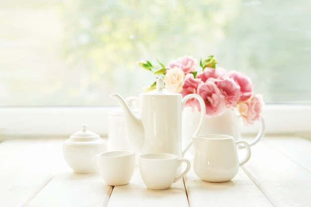Coffee set next to a vase of flowers on a table against  a window