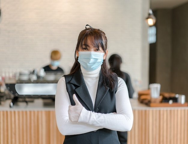 Coffee shop business owner wearing surgical mask.  confident business  woman