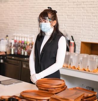 サージカルマスクを身に着けている喫茶店のビジネスオーナー自信のあるビジネスウーマン