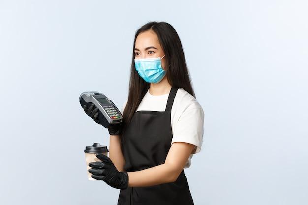 コーヒーショップ、コロナウイルス、社会的距離、非接触型決済の概念。医療マスク作業カフェ、コーヒーのテイクアウトとpos端末を渡すことでかわいいアジアの女の子
