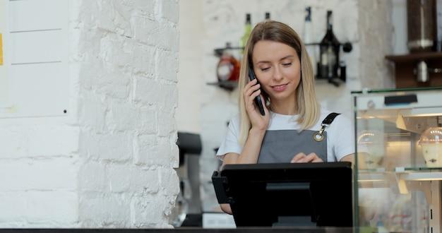 コーヒーショップの従業員が携帯電話で事前注文を受け付けます