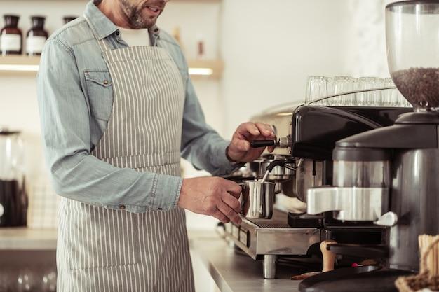 コーヒーショップ。ミルクでピッチャーを保持し、カプチーノのカップのためにそれを泡立てるハンサムなひげを生やした男。