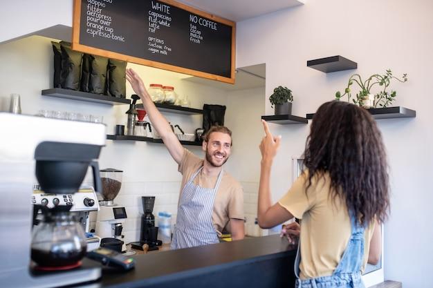 커피 숍, 메뉴. 메뉴와 여자 주문을 가리키는 커피의 선택을 제공하는 카운터에서 젊은 상냥한 남자