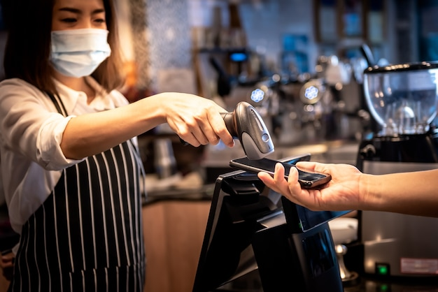 Coffee shop owner, asian woman accepting payments from customers with the use of a barcode scanner with the customer's mobile application, to people and new normal concept.