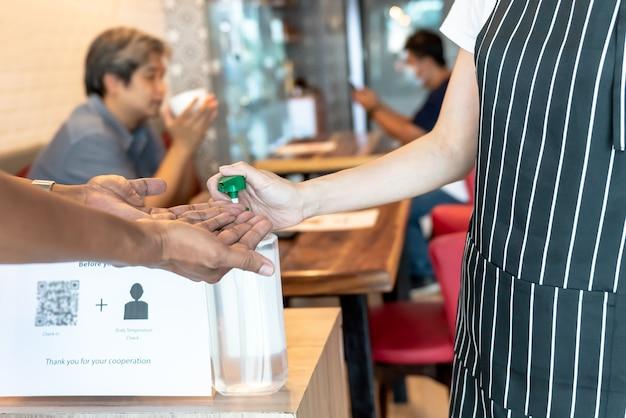 Владелец кофейни, обслуживающий клиентов, отжимающий спиртосодержащее дезинфицирующее средство для рук