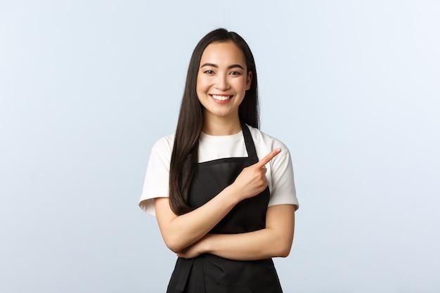 Кофейня, малый бизнес и концепция запуска. веселая азиатская девушка в фартуке работает ресторан или кафе, приглашая потребителей на специальное предложение. улыбающийся женский персонал указывая пальцем вправо.