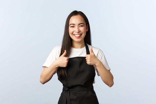 コーヒーショップ、中小企業、スタートアップのコンセプト。陽気な笑顔のアジアの女性カフェスタッフ、親指を立てて、エプロンを着て仕事でバリスタ。かわいい女の子の従業員は素敵な場所、おいしい料理を訪問することをお勧めします