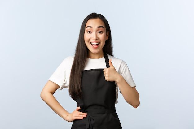 コーヒーショップ、中小企業、スタートアップのコンセプト。黒のエプロンを着た陽気な若いきれいな女性のカフェスタッフは、サポートやジェスチャーのようなものを示しています。アジアのウェイトレスは親指を立てて笑顔を満足させる
