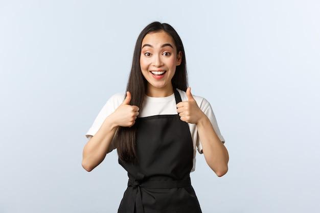 コーヒーショップ、中小企業、スタートアップのコンセプト。興奮した笑顔のアジアのウェイトレスが新しいメニューを承認します。黒のエプロンを着たかわいい女性のバリスタは、賛成または賛成の賛成で親指を立てます。