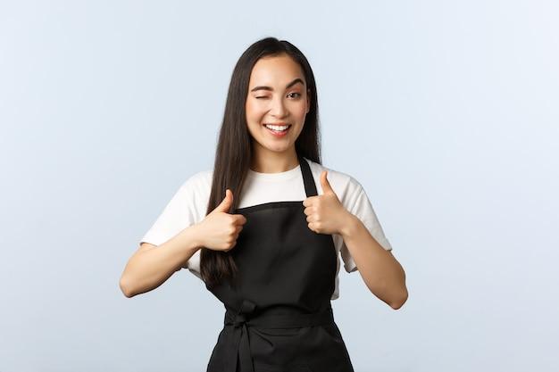 コーヒーショップ、中小企業、スタートアップのコンセプト。カフェやレストランでバリスタとして働いている黒いエプロンのフレンドリーな生意気なアジアの女の子は、親指を立てて、ウインクして、笑顔を見せて、新しいメニューを試してみてください