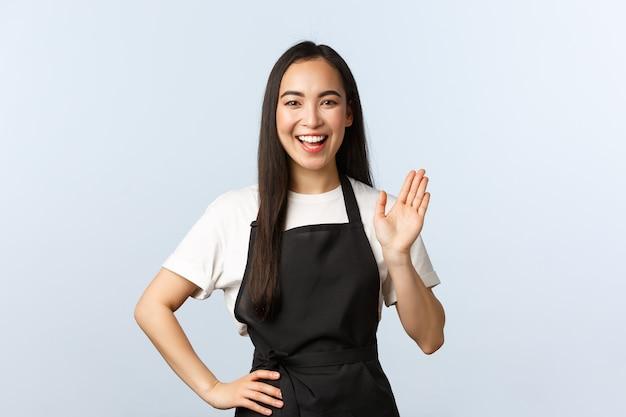Кофейня, малый бизнес и концепция запуска. дружелюбная улыбающаяся азиатская женщина-бариста приветствует клиента, приходящего в кафе, делая заказ. сотрудник девушки машет, чтобы поздороваться с потребителем.