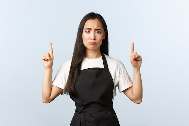 커피숍, 중소기업 및 시작 개념. 우울하고 슬픈 귀여운 레스토랑 웨이터가 손가락을 가리키고 있습니다. 검은 앞치마를 입은 화난 여성 아시아 바리스타