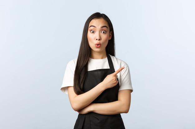 コーヒーショップ、中小企業、スタートアップのコンセプト。興味をそそられて驚いたかわいいアジアの女性バリスタ、カフェのウェイトレスが指を右に向け、唇を折りたたんで、すごい、面白いプロモーションに反応